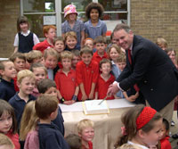 Richard Bacon MP cuts the cake to celebrate Little Melton First School's Artsmark Gold award.