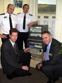 Richard Bacon MP (right) examines Wymondham's CCTV system with Jon Jarvis of First connect (kneeling, left) Inspector Andy Taylor (standing, right)and Sergeant John Cuthbert
